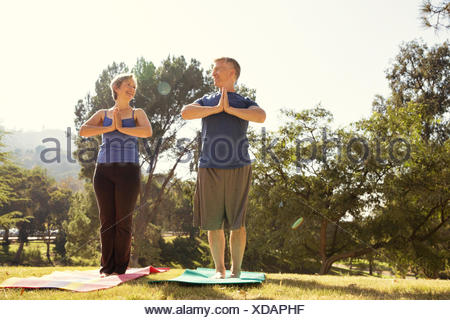 Mature couple practicing yoga in park - Stock Photo