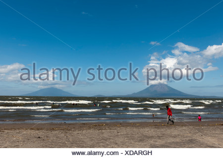 Shallow shore of the Lago de Nicaragua with the volcanic island of Ometepe and the stratovolcanoes Volcán Concepción, left - Stock Photo