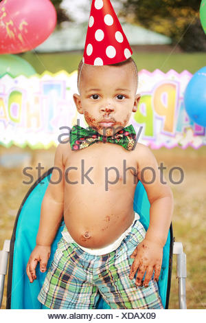 Portrait of a shirtless Boy at a birthday party with chocolate cake on his face and hands - Stock Photo