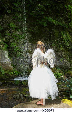 A girl with blond hair wearing an angel costume with feather wings stands at the edge of a tranquil pool; Oregon, United States - Stock Photo
