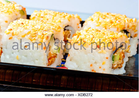 rolls with eel and sesame seeds on a black dish - Stock Photo
