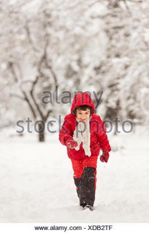 Boy running in snow - Stock Photo