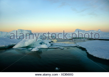 Evening red above water with ice-pack and icebergs Eastgreenland - Stock Photo