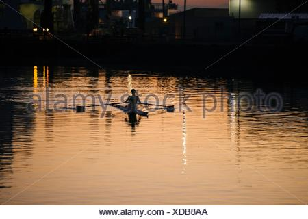 Young man rowing on river at sunset - Stock Photo