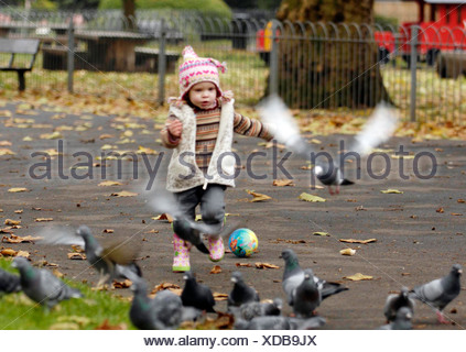 Female child wearing a patterned hat, striped jumper, grey waistcoat, grey jeans and pink floral rubber boots, running towards - Stock Photo