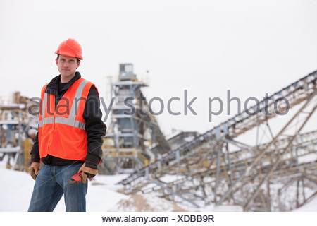 Engineer holding pipe wrench at a construction site - Stock Photo