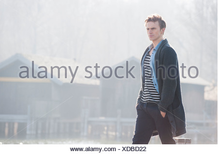 Mid adult man walking on pier, hands in pockets - Stock Photo
