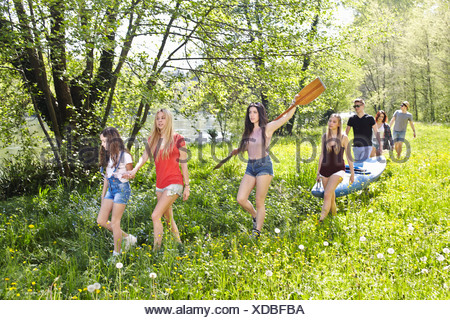 Group of friends walking through grass carrying canoe - Stock Photo