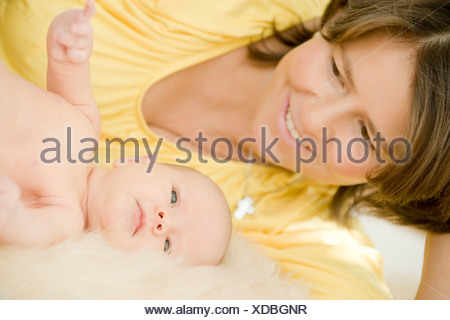 mother with her 1 month old baby on a fur - Stock Photo