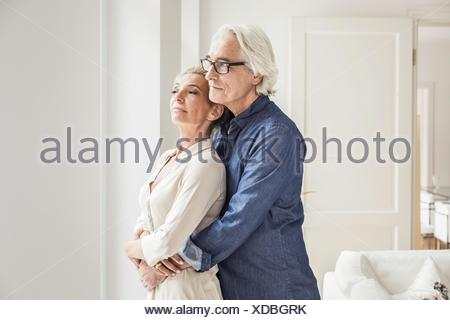Couple hugging, looking out of window - Stock Photo