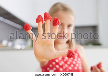 Girl putting raspberries on fingers - Stock Photo