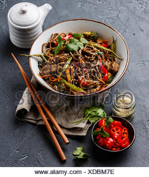 Stir fry noodles soba with beef and vegetables in bowl on dark stone background - Stock Photo