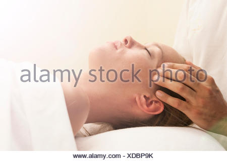 Side view of masseurs hands massaging head of young woman in spa - Stock Photo