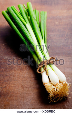 fresh spring onions on a wooden board - Stock Photo