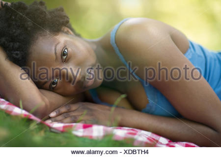 Portrait of young woman lying on side in park - Stock Photo