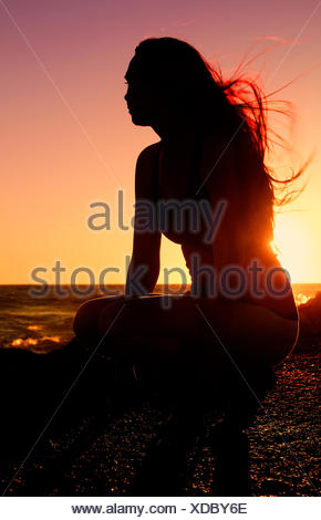 Silhouette of woman practising yoga on the beach at sunset - Stock Photo