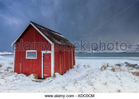 A typical house of the fishermen called rorbu on the snowy beach frames the icy sea at Ramberg Lofoten Islands Norway Europe - Stock Photo