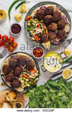 Turkish meatballs aka koftes served on pita bread on two copper plates with cold bean salad and red onions photographed from top view. Yogurt sauce, h - Stock Photo