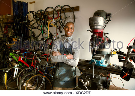 Mechanic in bicycle workshop with arms crossed - Stock Photo