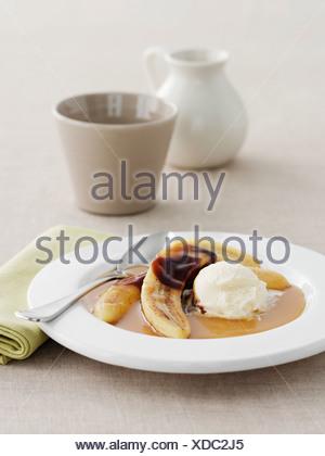 Plate of bananas, cream and sauce - Stock Photo