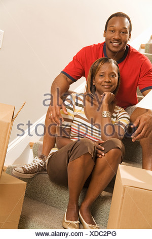 African couple sitting on stairs - Stock Photo