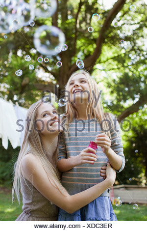 Mother and daughter watching floating bubbles in park - Stock Photo