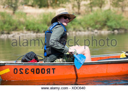 A Boy Scout paddles his canoe down the Clearwater River near Orofino, Idaho while traveling on the original Lewis and Clark Trail and canoe route. - Stock Photo