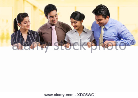 Businesspeople holding a placard - Stock Photo