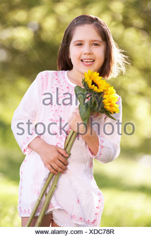 Young Girl Walking Through Summer Field Holding Sunflower - Stock Photo