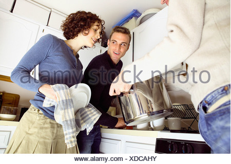 Friends standing in kitchen - Stock Photo