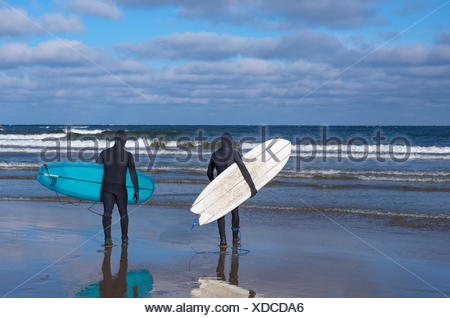 Finland, Pohjanmaa, Vexala, Rear view of surfers in wetsuits on beach - Stock Photo
