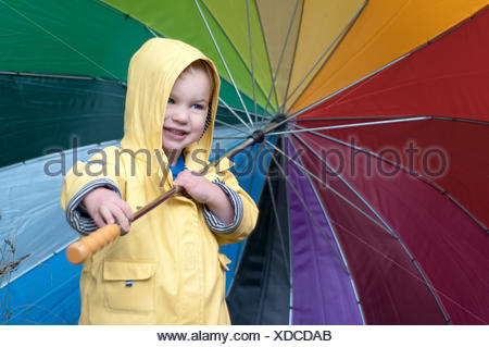 Boy in a rain coat holding multi-colored umbrella - Stock Photo