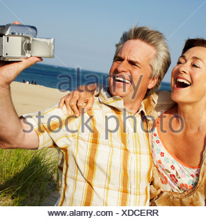 Close-up of a mature couple taking a picture of themselves on the beach - Stock Photo