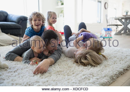 Family laying and relaxing on shag rug - Stock Photo