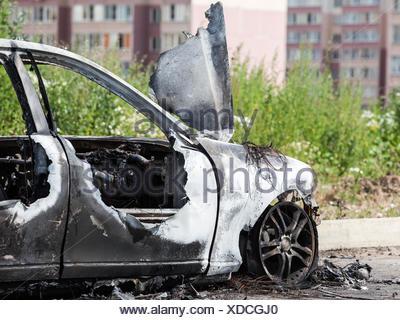 Arson fire burnt wheel car vehicle junk - Stock Photo