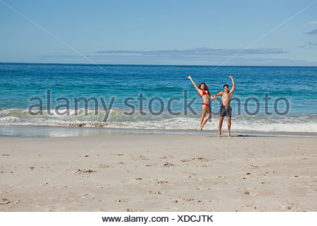 Portrait of a happy couple in swimsuit jumping - Stock Photo
