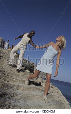 Coast, stairs, couple, skin colour differently, hand in hand, happy, man, non-white, woman, blond, young, partnership, nationality, difference, mixed race, flirtation, vacation, holiday acquaintance, holiday love, summer - Stock Photo