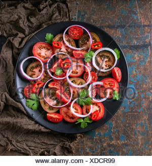 Black plate with sliced different tomatoes, red onion and parsley salad, served on wet sackcloth rag over old dark wood textured - Stock Photo