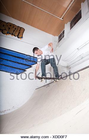Skateboarder on ramp at skate park - Stock Photo