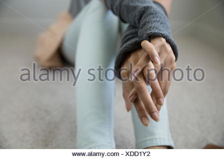 Close up young woman with hands clasped - Stock Photo
