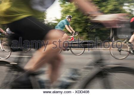 Close up of racing cyclists speeding on urban road in racing cycle race - Stock Photo