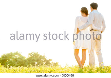 Rear view of loving couple standing arms around against clear sky - Stock Photo