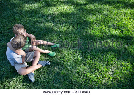High angle view of two brothers with arms around each other in garden - Stock Photo