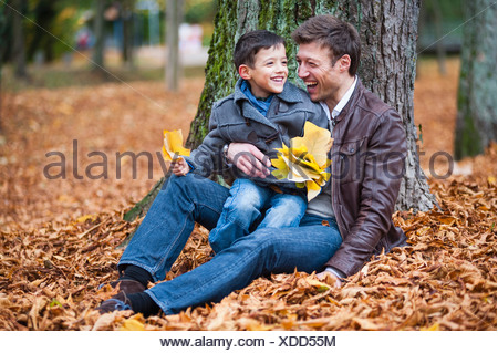 Young boy and father sitting on autumn leaves in park - Stock Photo
