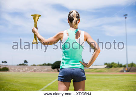 Rear view of female athlete holding a fire torch - Stock Photo
