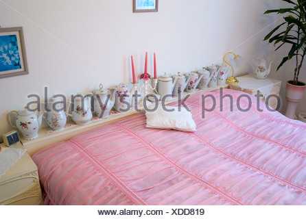Old fashioned bedroom with pink bedspread and teapots, Germany, Europe - Stock Photo