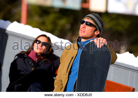Mid adult man holding a snowboard with a young woman in the background - Stock Photo