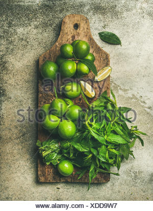 Flatlay of freshly picked organic limes and mint leaves for making cocktail or lemonade on wooden rustic board over grey concrete stone background, to - Stock Photo