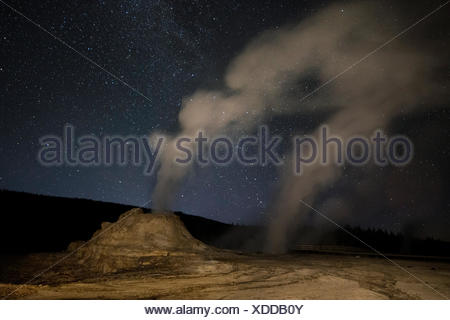 Milky Way above Castle Geyser emitting steam. - Stock Photo
