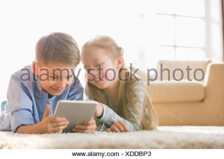 Brother and sister using digital tablet on floor at home - Stock Photo